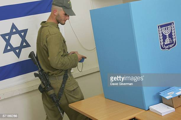 An Israeli soldier enters the voting booth to choose between 31 different political parties before voting on March 26 2006 in an army base at Rosh...