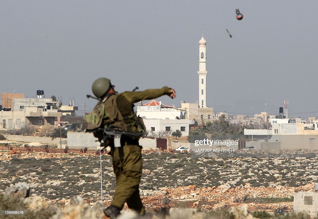 An Israeli soldier fires a tear gas canister at Palestinian protestors during clashes in the northern West Bank village of Qusra on January 1, 2013. Israeli security officials have noted a rise in the number of violent incidents in the West Bank since last month's United Nations vote to raise the Palestinians' diplomatic standing.