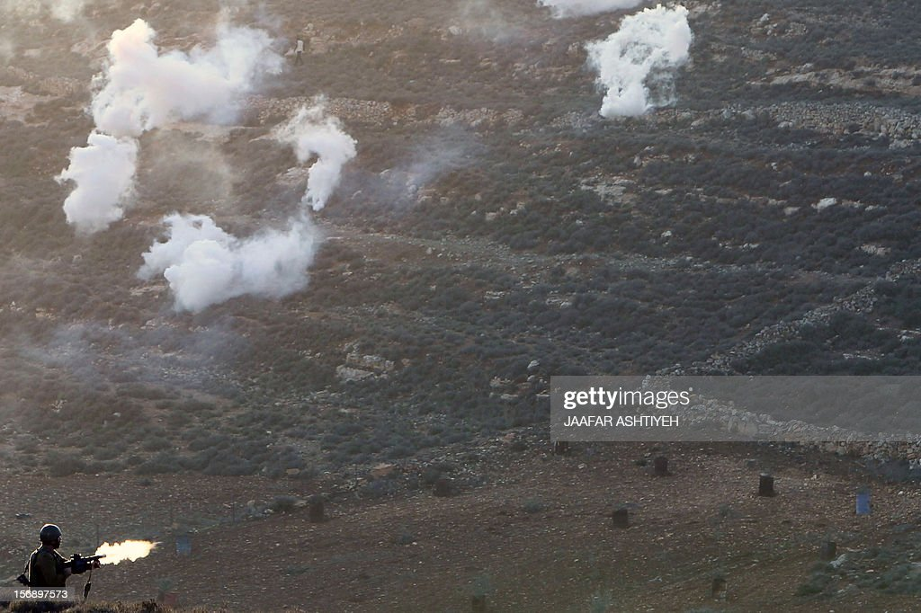 An Israeli soldier fires during clashes with Palestinians after Israeli settlers attacked villagers in the northern West Bank village of Qusra on November 24, 2012. PHOTO