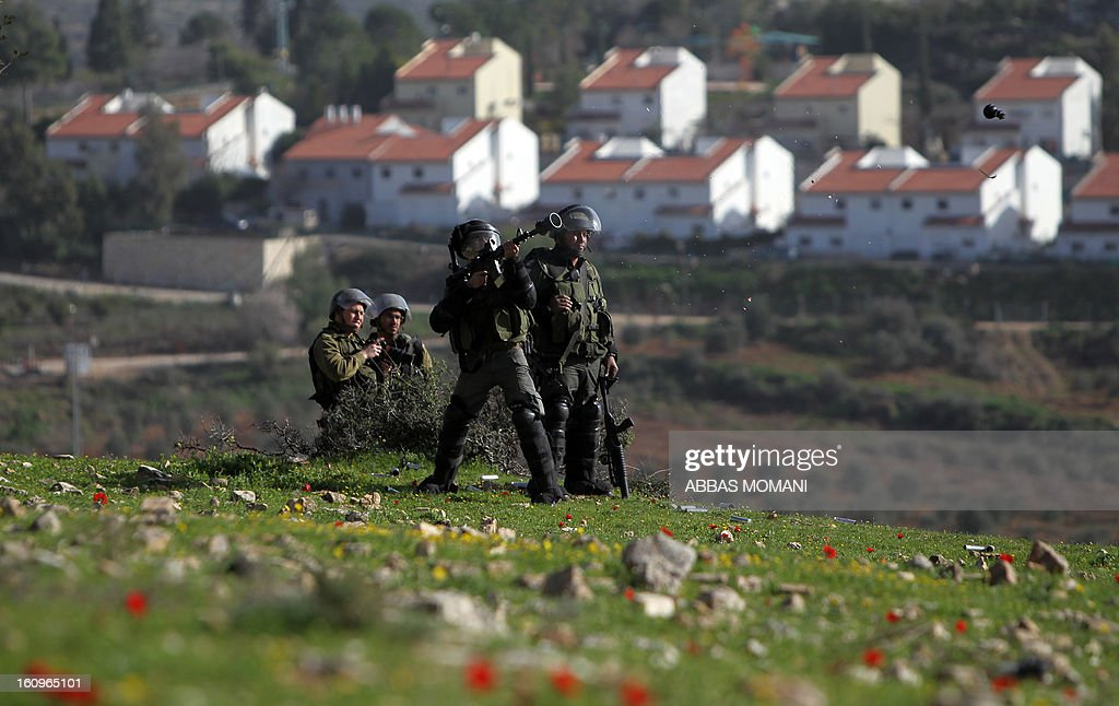 An Israeli soldier fires tear gas towards Palestinian protesters throwing stones during clashes following a demonstration organised by residents of the West Bank village Nabi Saleh to protest against the expansion of Jewish settlements on Palestinian land on February 8, 2013.