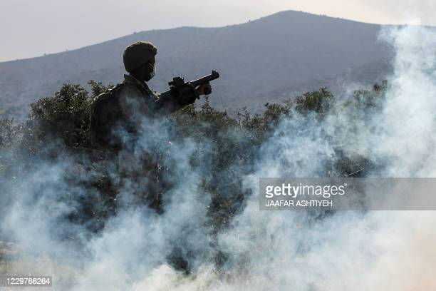 An Israeli soldier fires teargas against Palestinian protesters during a protest against Jewish settlements on November 24 in the Jordan Valley in...