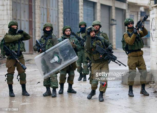 An Israeli soldier fires teargas towards Palestinian demonstrators during a demonstration in al-Aroub Palestinian refugee camp, between the West Bank...