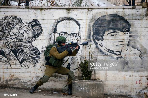 TOPSHOT An Israeli soldier fires teargas towards Palestinian demonstrators during a demonstration in alAroub Palestinian refugee camp between the...