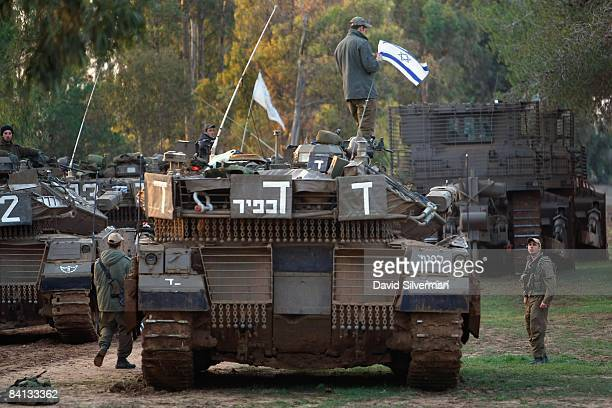 An Israeli soldier fixes a national flag to his tank before heading out on tank patrol on December 29 2008 along Israel's border with the Gaza Strip...