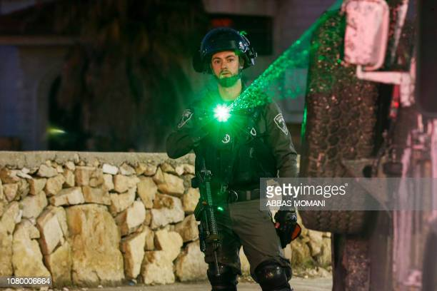 An Israeli soldier flashes a light during clashes with Palestinian protesters in the West Bank city of Ramallah on January 10 2019
