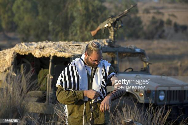 An Israeli soldier from a tank squadron wearing 'Talit' and 'Tefilin' conducts morning prayers at an Israeli army deployment area near the IsraelGaza...