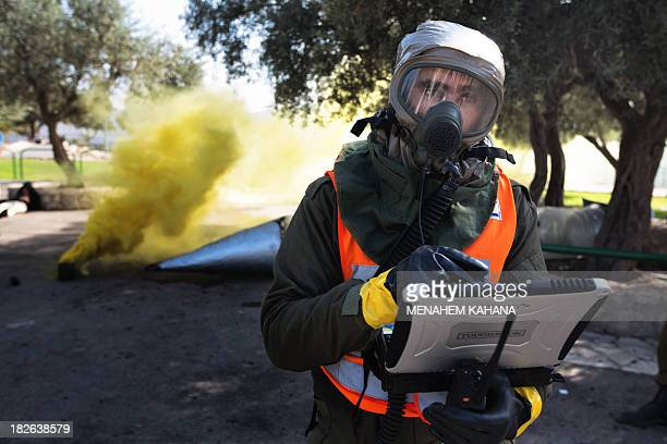 An Israeli soldier from the army's Home Front Command wearing a chemical warfare suit takes part in a defence drill simulating a chemical missile...