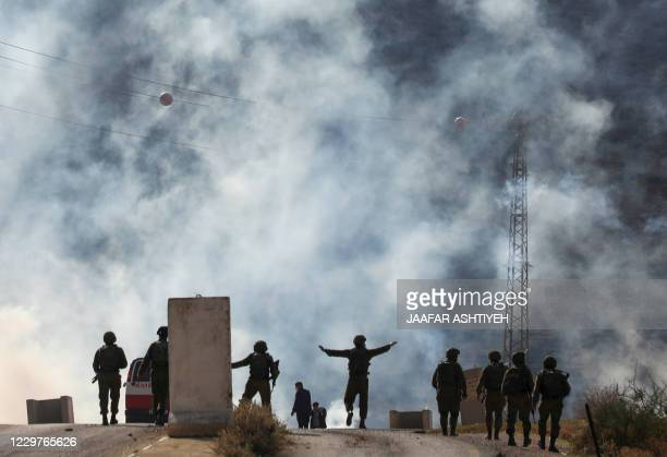An Israeli soldier gestures during a protest by Palestinian demonstrators against Jewish settlements on November 24 in the Jordan Valley in the...