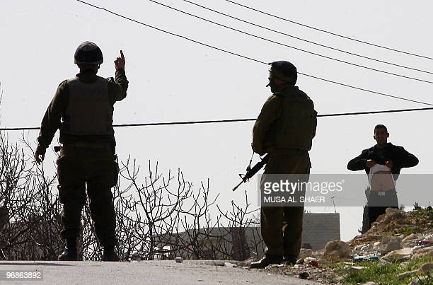 An Israeli soldier gives an order to a Palestinian protester to lift his shirt during a demonstration against Israel's separation barrier in the West...