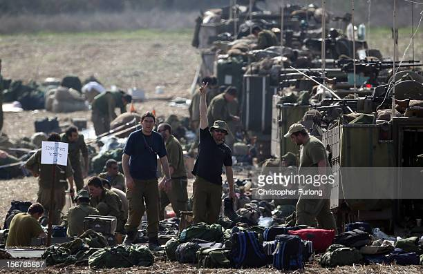 An Israeli soldier gives the victory sign as mechanised infantry check their equipment in a forward staging area on November 21 2012 on Israel's...