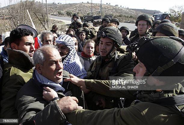 An Israeli soldier grabs APTN cameraman Eyad Hamad as Palestinians and foreign peace activists protest against the construction of the controversial...
