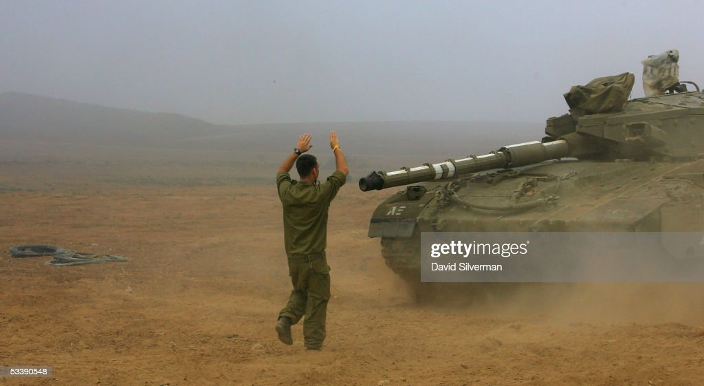 An Israeli soldier guides a Merkeva tank into place in the morning mist near the border with the Gaza Strip August 15, 2005 in the fields of Kibbutz Mefalsim in southern Israel. The Israeli army has deployed hundreds of tanks and armored vehicles and thousands of troops to defend the Jewish state's historic withdrawal from the Gaza Strip after a 38-year occupation.