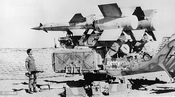 An Israeli soldier holding an AK-47 looks at a Soviet-built Egyptian SAM III missile launcher captured by Israeli forces on the western bank of the...