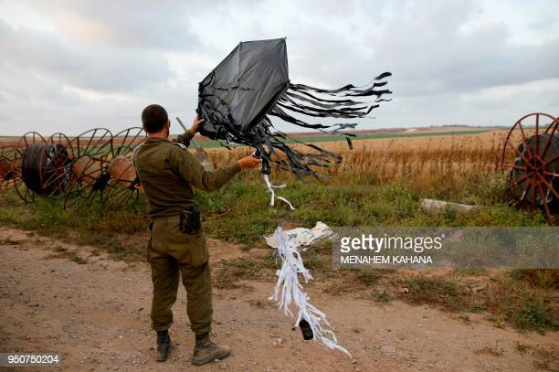 TOPSHOT An Israeli soldier holds a kite flown over the border from Gaza in a tactic recently used by Palestinian protestors to start small fires in...