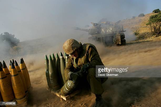 An Israeli soldier holds on to a 155mm artillery shell as a mobile cannon opens fire during a barrage against Hezbollah targets in South Lebanon July...