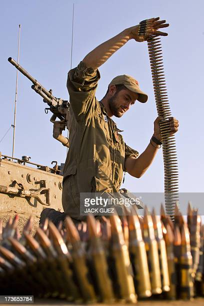 An Israeli soldier inspects an ammunition belt for a machine gun of a Merkava tank stationed in the Israelioccupied Golan Heights on July 16 after...