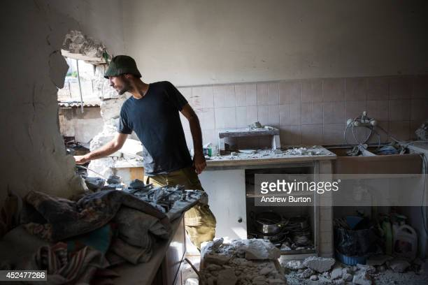An Israeli soldier inspects an Israeli home allegedly hit by a Hamas rocket on July 21 2014 in Sderot Israel Yesterday marked the bloodiest day of...