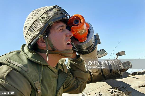 An Israeli soldier inspects the firing sights through the cannon on a Merkava tank, as another soldier inspects the tracks after coming off duty near...