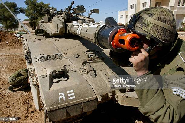 An Israeli soldier inspects the firing sights through the cannon on a Merkava tank as another soldier inspects the tracks after coming off duty near...