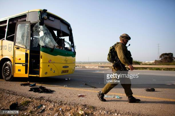 An Israeli soldier inspects the site where an Israeli teenager was critically wounded when a projectile from Gaza slammed into a bus taking children...