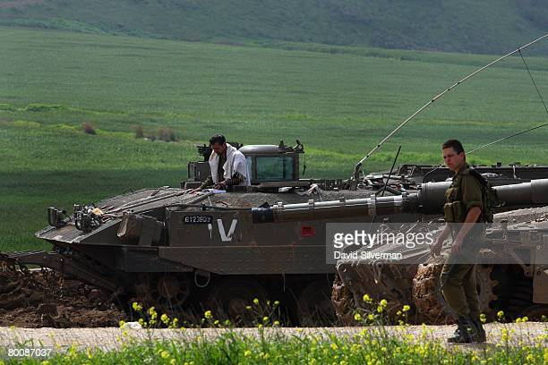 An Israeli soldier is wrapped in a prayer shawl as he recites his morning prayers standing in an armored fighting vehicle after withdrawing from...