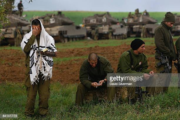 An Israeli soldier is wrapped in a Tallit a Jewish prayer shawl as he recites his morning prayers at an advance deployment area on December 30 2008...