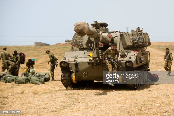 An Israeli soldier jumps off a tank as he is smoking a cigarette after Israel and Hamas agreed on a ceasefire on May 21, 2021 in Sderot, Israel....