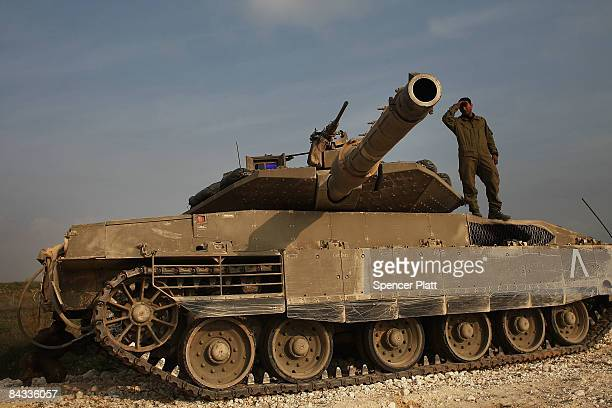 An Israeli soldier, just back from Gaza, stands on top of his tank on January 17, 2009 along the Gaza-Israeli border in Israel. While fighting...