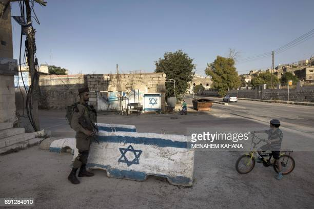 An Israeli soldier keeps watch as the children of Israeli settlers play outside the Abraham Avinu settlement in the divided West Bank city of Hebron...