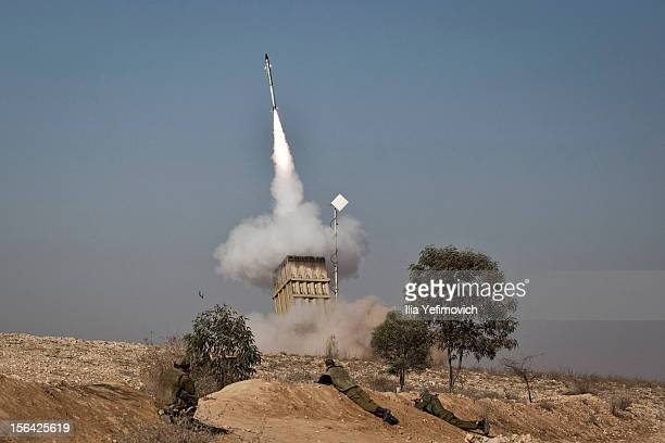 An Israeli soldier lies on the ground as missiles are fired from an Iron Dome anti-missile station on November 15, 2012 near the city of Beer Sheva,...
