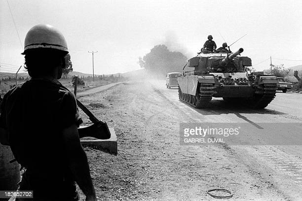 An Israeli soldier looks an Israeli Britishmade Centurion tank moving forward the Syrian front lines on the Syrian Golan Heights on October 12 1973 a...