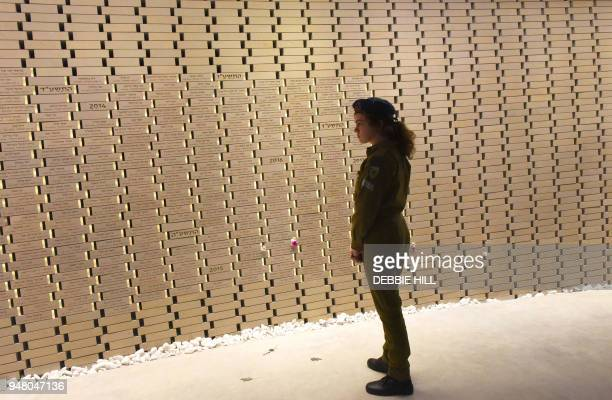 TOPSHOT An Israeli soldier looks at the names of fallen soldiers in the National Memorial Hall For Israel's Fallen before the official ceremony for...
