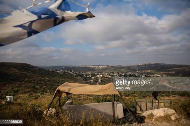 An Israeli soldier looks at the Palestinian village of Kfar Kadum as she is guarding the Jewish settlement of Har Hemed near Nablus on June 26, 2020...