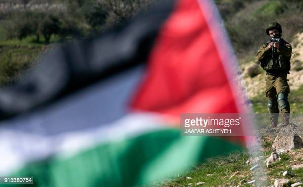 An Israeli soldier looks through the scope of an assault rifle as a Palestinian protester raises a Palestinian flag during clashes following a...