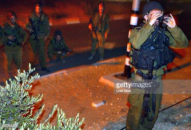 An Israeli soldier looks throw his night vision devise as his comrades take positions during exchanges of fire in the Jewish Gaza Strip settlement of...