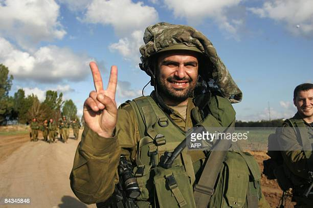 An Israeli soldier makes the V sign on the IsraelGaza border as he returns from the Gaza Strip on January 18 2009 Israel and Palestinian fighters...