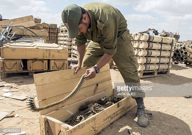 An Israeli soldier packs bullets at an army deployment along the border between Israel and the Hamascontrolled Gaza Strip on July 25 2014 Israeli...