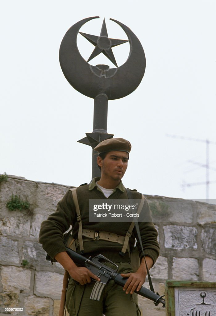 An Israeli soldier patrols his post in Beit Omar during a Palestinian uprising. Violence broke out after rebel Israeli and Palestinian fighters protested in the occupied territory of Gaza during the first Intifada. | Location: Beit Omar, West Bank.