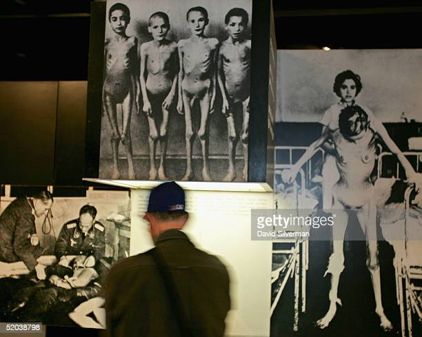 An Israeli soldier pauses alongside photos of Jewish medical experiment victims in an exhibition dedicated to the Nazi death camps during their visit...