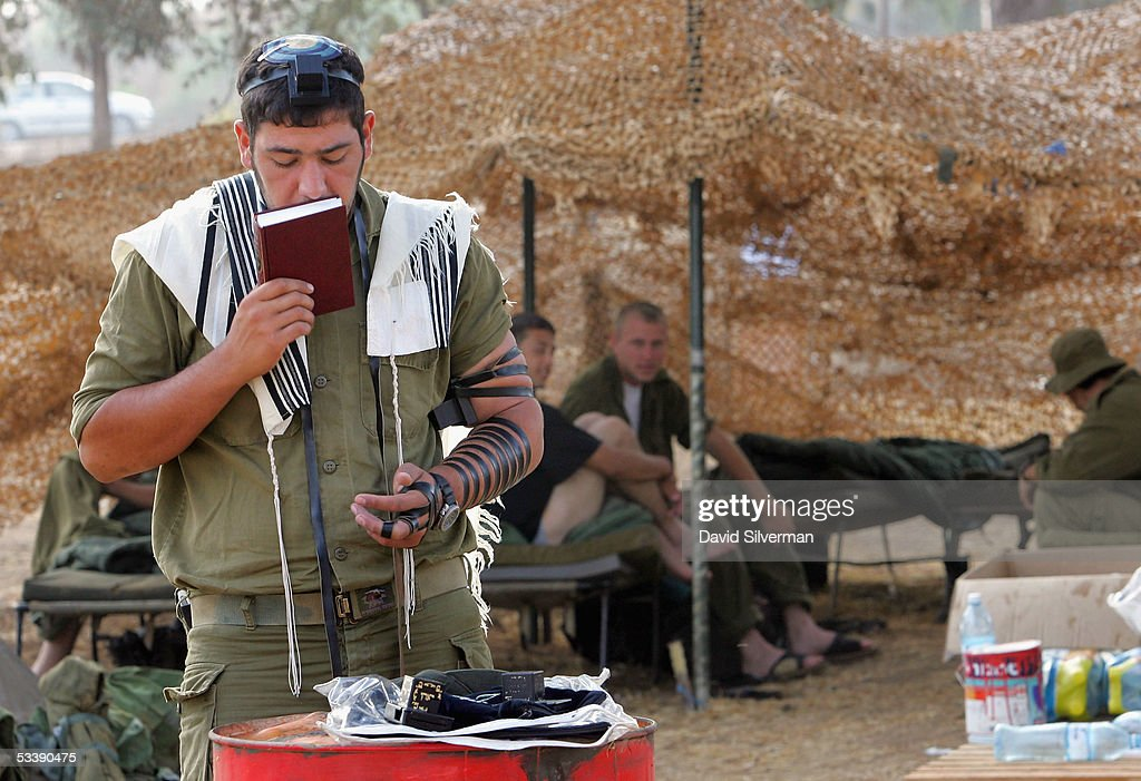 An Israeli soldier performs his morning prayers as others wake up under camouflage netting near the border with the Gaza Strip August 15, 2005 in the fields of Kibbutz Mefalsim in southern Israel. The Israeli army has deployed hundreds of tanks and armored vehicles and thousands of troops to defend the Jewish state's historic withdrawal from the Gaza Strip after a 38-year occupation.