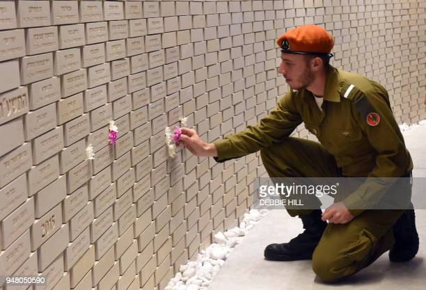 An Israeli soldier places a flower on the name of a fallen soldier in the National Memorial Hall For Israel's Fallen before the official ceremony for...