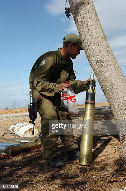 An Israeli soldier places a tank shell next to a tree as his army unity keep its position on the border with the Gaza Strip on December 31 2008 A...
