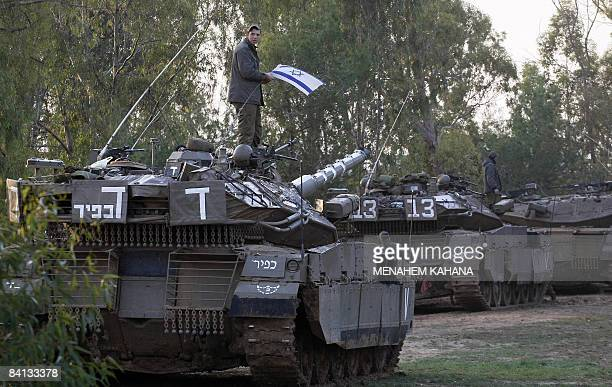 An Israeli soldier places his national flag on his tank as troops take position on the Israeli border with the Gaza Strip on December 29 2008 Israeli...