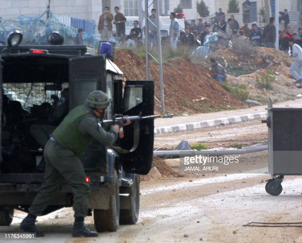 An Israeli soldier points his gun at Palestinian youths during clashes in the West Bank town of Ramallah 28 December 2001 Israeli Foreign Minister...