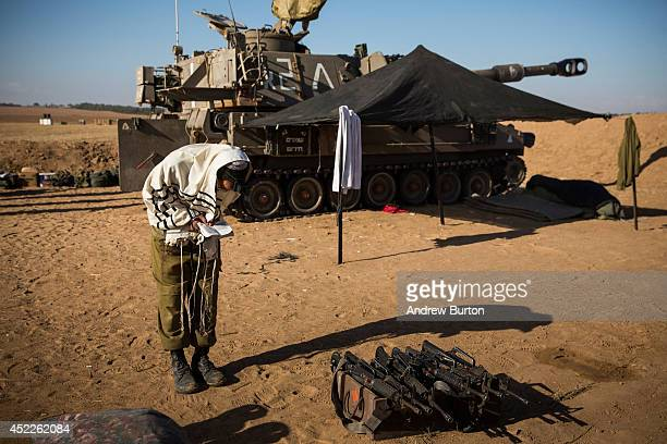An Israeli soldier prays after helping fire artillery shells into Gaza on July 17 2014 near Sderot Israel As the Israeli operation 'Protective Edge'...