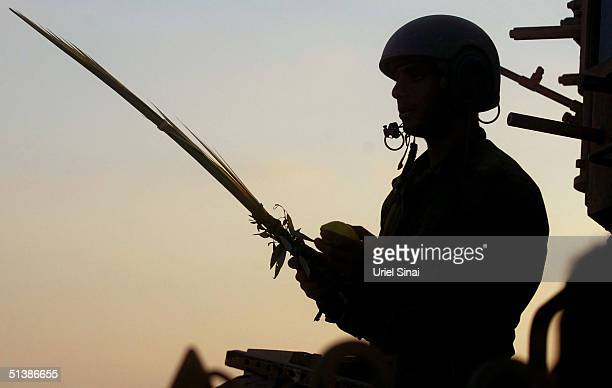 An Israeli soldier prays as he returns for rest from the Gaza Strip with the four plants of Sukkot the Jewish feast of the Tabernacles October 3 2004...