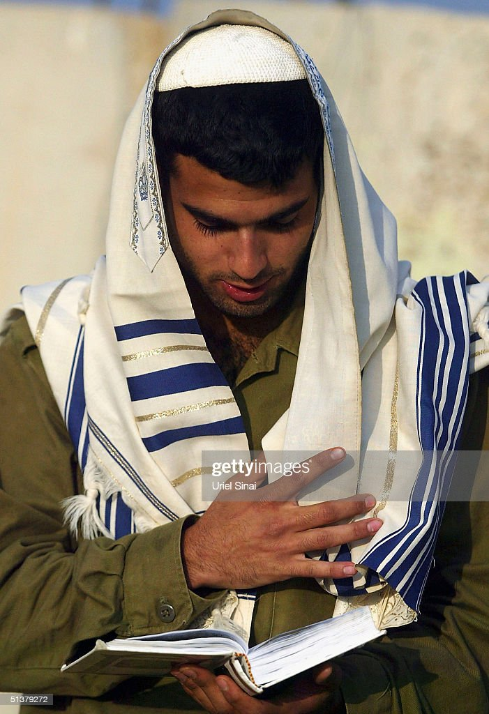 An Israeli soldier prays at a temporary army base outside the Gaza Strip during what an Israeli military spokesman has said is an 'open-ended' military operation on October 1, 2004 near the Israeli Mefalsim Kibbutz in the Gaza Strip. The Israeli Army prepare to continue its incursion into Jabaliya refugee camp and the towns of Beit Hanoun and Beit Lahiya after heavy attacks left thirty dead yesterday.