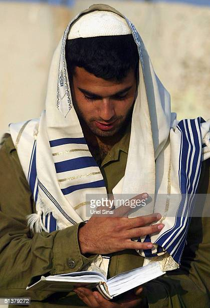 An Israeli soldier prays at a temporary army base outside the Gaza Strip during what an Israeli military spokesman has said is an 'open-ended'...