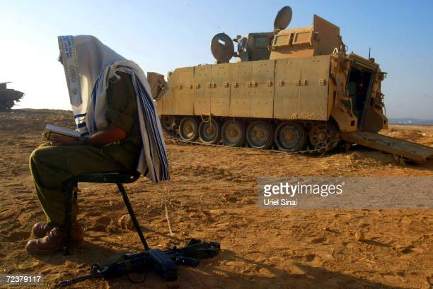 An Israeli soldier prays in Kibbutz Mefalsim after a night of fighting at the Jabalia refugee camp in the northern Gaza strip on October 5, 2004 in...