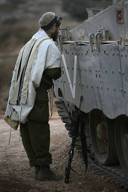 an israeli soldier prays next to a tank on september 21 2006 near the israeli